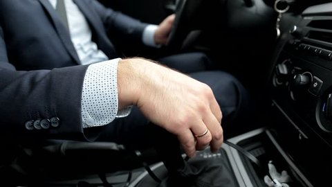 Respectable, responsible man driving car. Raining day. Dangerous road. The man in a suit. The man holds the lever. Close up