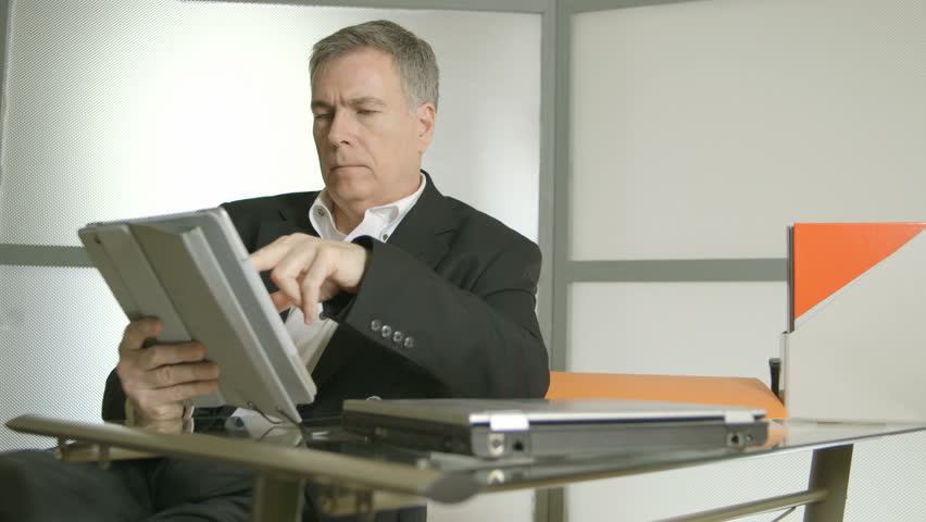 A Handsome Businessman In His Office Working With An Electronic Tablet Pc Closed