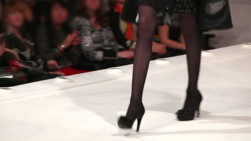 Model walks the runway, black shoes close-up in fashion house