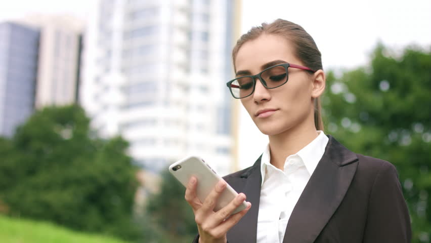 Young attractive businesswoman making phone call outdoors on park and city buildings background   Shutterstock HD Video #31999570