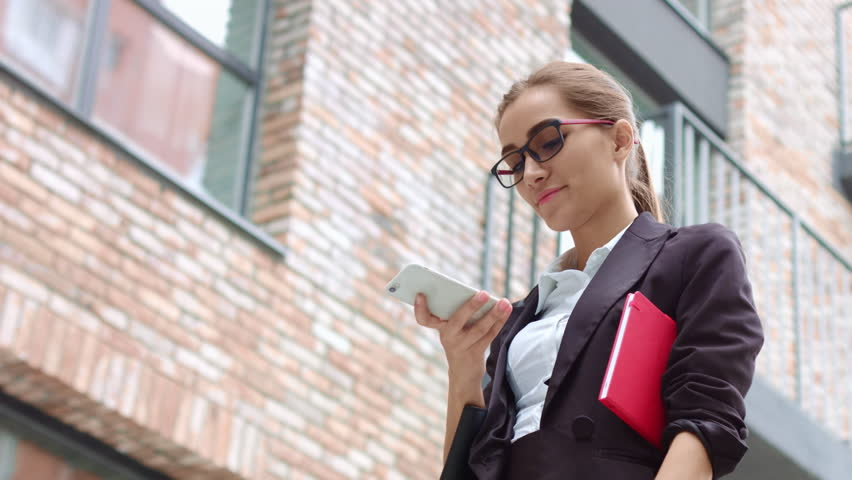 Low angle shot of young attractive woman in black suit and glasses make phone call outdoors with brick building on the background | Shutterstock HD Video #31999630