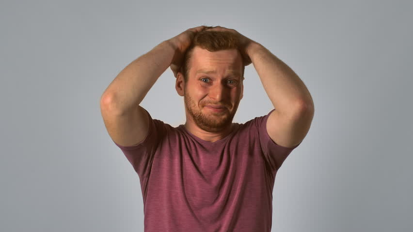 Caucasian guy with red hair showing emotion making terrible mistake. handsome redheaded men wearing in casual t-shirt. Portrait ginger young caucasian man on grey background | Shutterstock HD Video #32003350