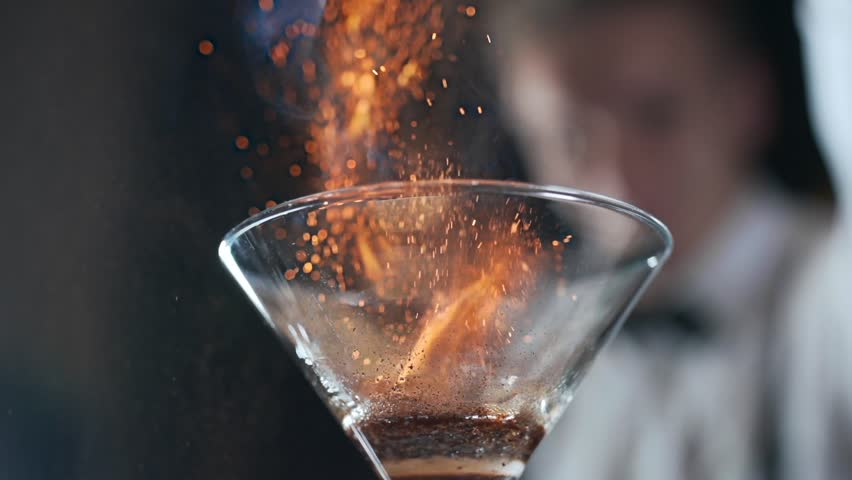 Bartender sets fire to cocktail, burning cinnamon in alcohol drink, 240 frames per second, barman makes drink