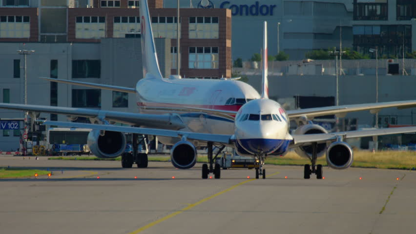FRANKFURT AM MAIN, GERMANY - JULY 21, 2017: British Airways Airbus 320 G-EUPO taxiing and China Eastern Airbus 330 B-5938 towing to service. Fraport, Frankfurt, Germany