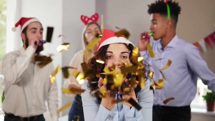 Young attractive woman blowing golden confetti from hands wearing christmas hat while her co-workers partying in the background in the office celebrating Christmas and New Year. Slowmotion shot