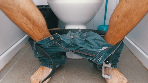 The Legs of a Man Sitting and Stand up from Toilet. A man in jeans and bare feet in a white toilet cubicle sits down on the toilet. Defecation process. Toilet in a public place.