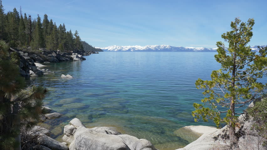 Zooming out and panning view of Lake Tahoe from its east shore, with the snowcapped Sierra Nevada peaks in the background.