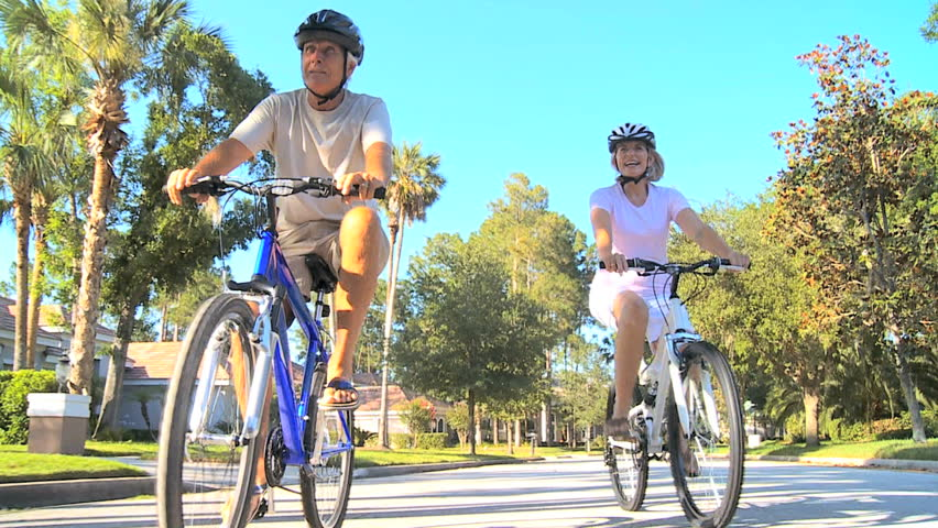 Senior couple keeping fit in their retirement on their bicycles in the sunshine on suburban roads