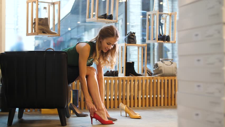 sale, shopping, fashion and people concept - young woman choosing heeled peep toe shoes at store