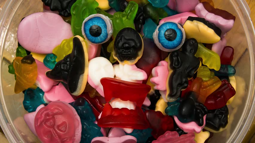 A halloween candy monster in a bowl of haloween candy eyeballs glaring at one on top of sweets someone taking an piece to eat. | Shutterstock HD Video #32150590
