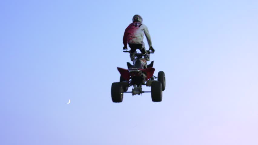Freestyle atv riders doing back to back cliffhangers trick with moon for background
