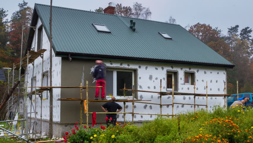 DWUKOLY, POLAND, October 21, 2017: Workers renovating a house facade at bad autumn weather. 4k time-lapse.