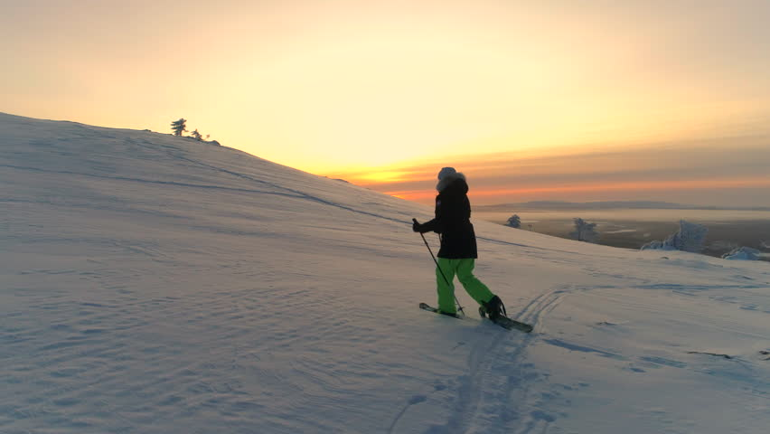 AERIAL Active woman in winter clothes snowshoeing on snowy mountain slope at sunrise. Young woman snowshoe hiking at winter sunset. Traveler snowshoe exploring snowy Lapland mountains in sunny morning