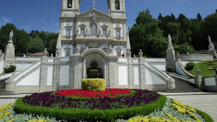 Tenoes near Braga. Sanctuary of Bom Jesus do Monte in neoclassical style and prospective view of bloom gardens in a sunny day, blue sky. Popular landmark and pilgrimage site in northern Portugal.