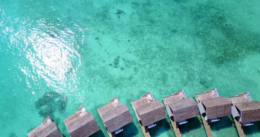 v09434 five 5 star resort water bungalows in Maldives with drone aerial flying view on white sand beach on tropical island