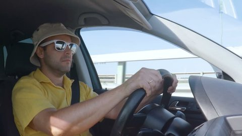 A man in a checked shirt and a baseball cap behind the wheel of a car. Man driving a car. Guy in a hat and sunglasses.