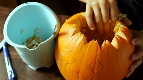 Young teen boy carving a pumpkin for Halloween on a table