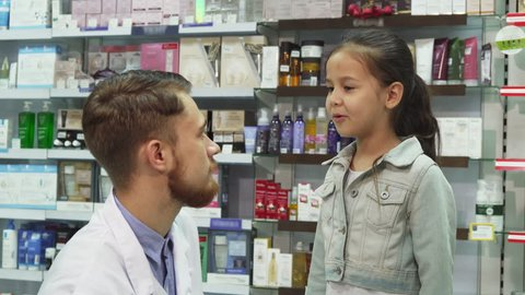 de94afdcfe5 She is unwell and he gives her the necessary pills. She smiles and shakes  his hand. Mom and daughter are in the pharmacy