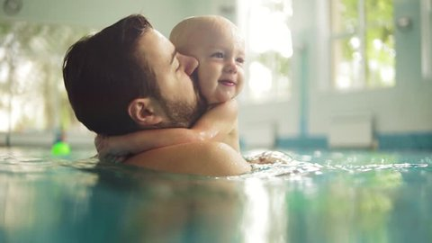Cute little baby and his father having swimming lesson in the pool. The father is holding his son in his hands and embracing him. Little boy is happily smiling