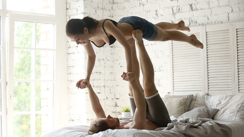 Fit sporty couple practicing acro yoga with partner together on bed, performing front plank bird pose, young man holding flying womans arms balancing on his feet, doing acrobatic exercise at home | Shutterstock HD Video #32239270