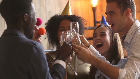 Multi-ethnic young people celebrating in festive atmosphere, diverse friends in party hats clinking glasses, drinking champagne congratulating each other with toast, wishing happy new year