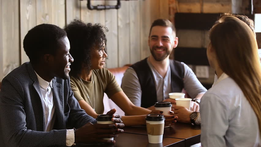 Multiracial friends drinking coffee together in cozy cafe, mixed race buddies talking sharing news having fun at meeting in cafeteria, diverse millennials chatting spending time in bar after work