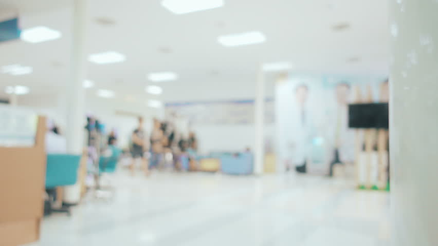 Locked Shot With Movement And Blurred Unidentified People Walking At Hallway Of Hospital
