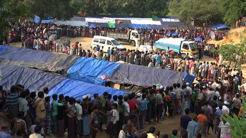TEKNAF, BANGLADESH - OCTOBER 25, 2017: A long queue of Rohingya refugees who have escaped Myanmar into Bangladesh, are standing and waiting in a long line for the food emergency relief distribution