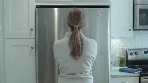 Young female standing in front and center of a closed double door fridge and opening them with both hands together
