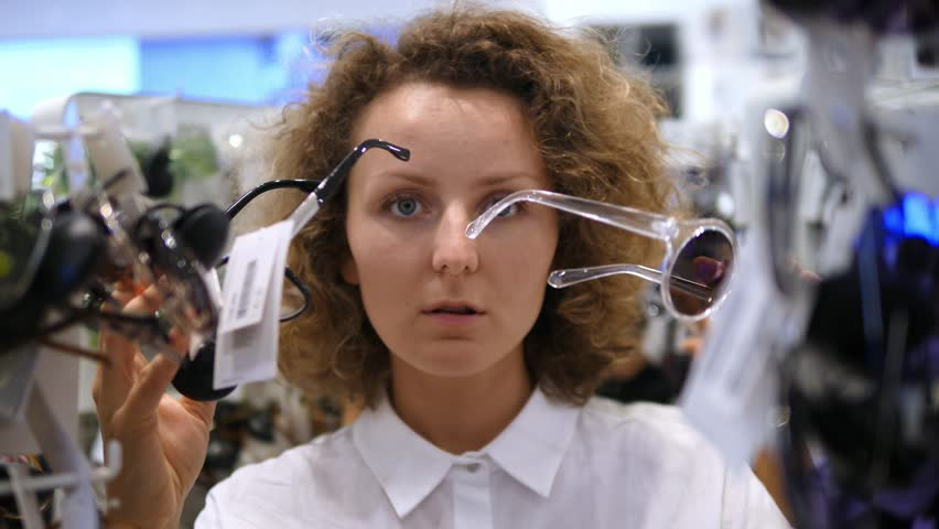 Shopping Woman Trying On Sunglasses In Shop With Accessories. 4K.