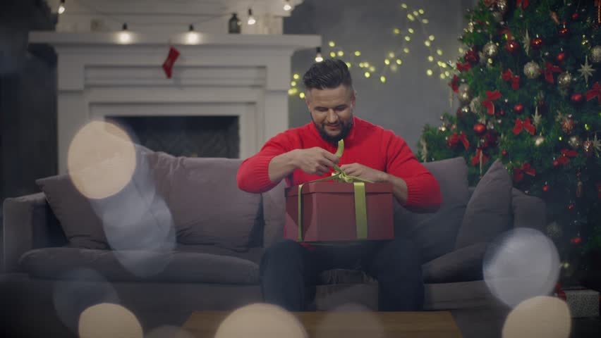Young man with Christmas present in hands opening it sitting on couch