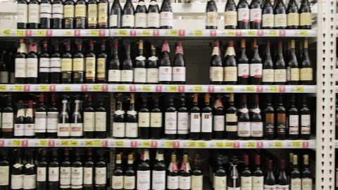 a lot of wine on the shelves in the supermarket. Alcoholic shop. travel by camera on bottles of wine