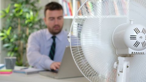 The video is about a sweaty man employee trying to refresh himself because of summer heat with a fan.Shot focus is fixed on the fan ventilator and the businessman acts out of focus on the background