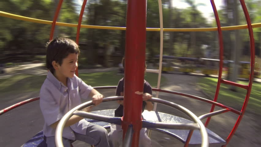 Hispanic Kid Brothers Play on Spinning Sphere at Public Playground. Inside View
