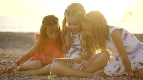 children on a beach are playing with modern device, watching cartoons and playing in apps
