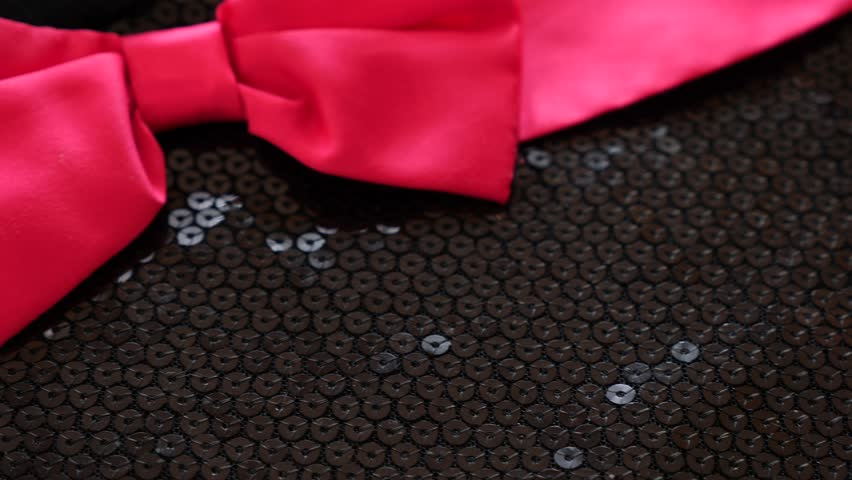 fabric as background. 4k, slow movement, black knitted fabric with paillettes. scarlet bow