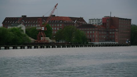 May, 2017 Berlin, Germany. Spree river with old crane and brick buildings on a cloudy day.