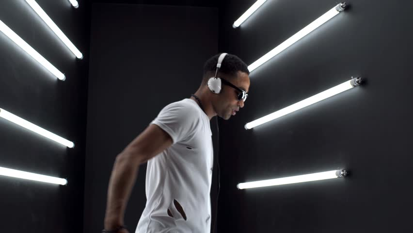 young hipster handsome black man dancing hip hop style, listening to music on headphones, close up legs, sneakers, neon light, disco party club, white apparel, smiling, happy, having fun, positive