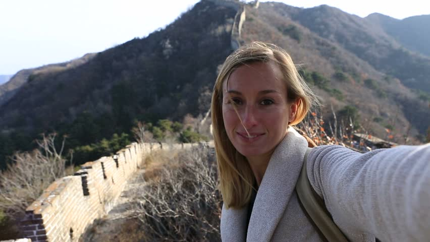 Young woman traveling Asia, stands on the Great Wall of China taking selfies. Young woman traveling taking selfies on the Great Wall of China