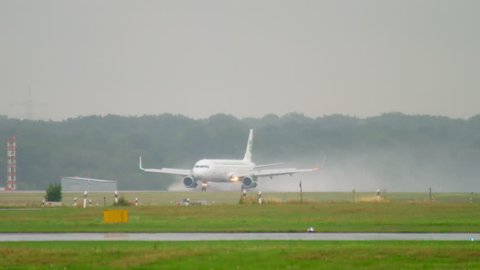 DUSSELDORF, GERMANY - JULY 24, 2017: Germania Airbus 321 D-ASTE braking after landing at rain. Dusseldorf airport