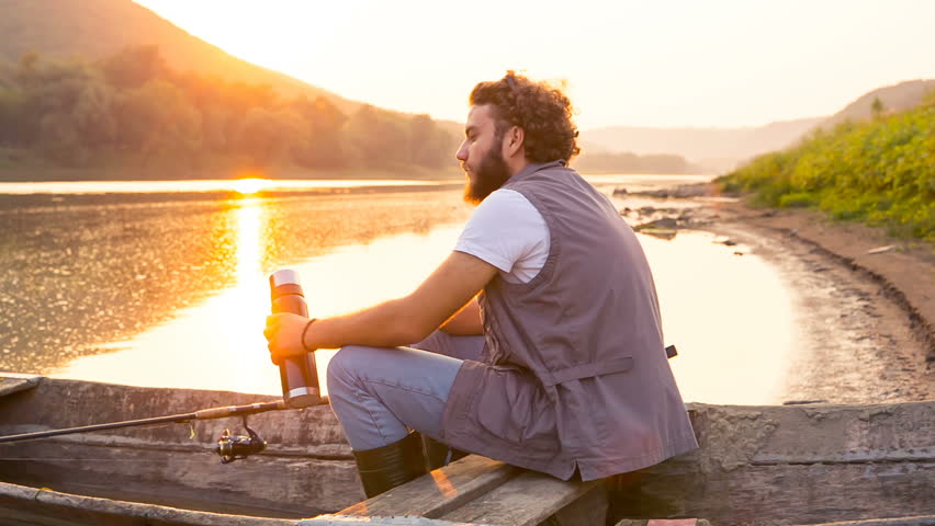 Stylish hipster with thermos at sunset. Fisherman in an old wooden boat on a summer evening