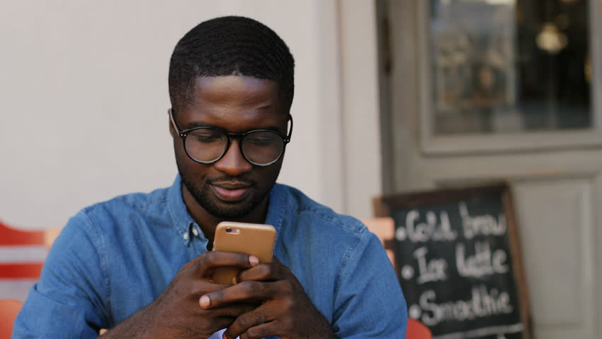 6220b5493006 Portrait of young handsome african american man with beard in glasses  looking at cell phone in cafe. Guy resting and typing message.