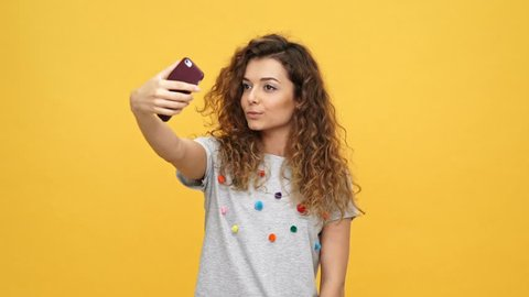 Smiling happy curly woman in t-shirt making selfie on smartphone over yellow background