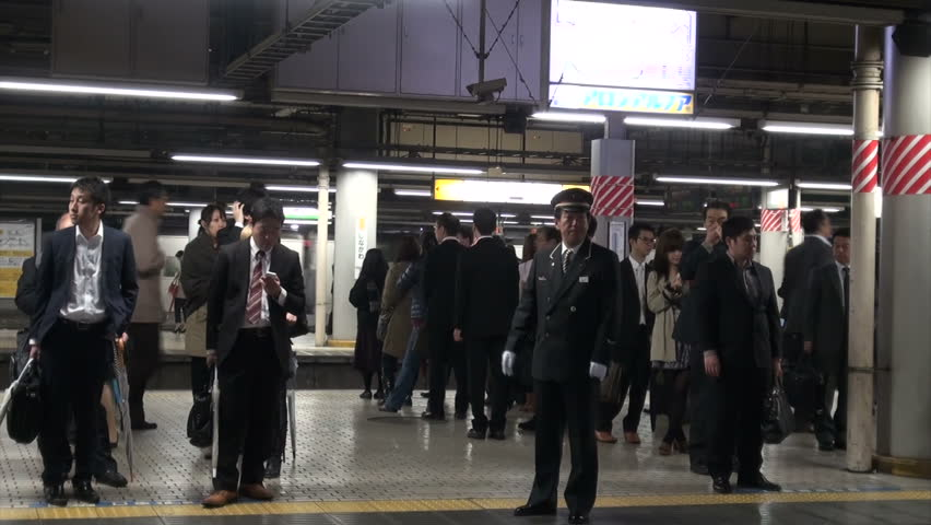 TOKYO, JAPAN - 6 NOVEMBER 2012: Commuter train leaves from platform of Shinagawa station, conductor visible in the background, in Tokyo