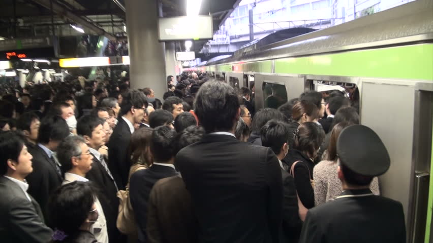 TOKYO, JAPAN - 6 NOVEMBER 2012: Handheld video of commuting passengers pushing their way into a local train at a major train station in Tokyo, Japan