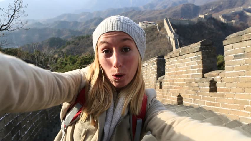 Young woman travelling Asia, stands on the Great Wall of China taking selfies. Young woman travelling taking selfies on the Great Wall of China