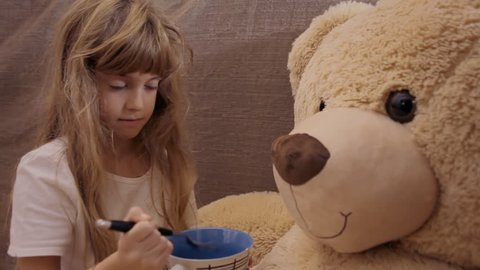 A cute little girl feeding her friend, a giant teddybear, with a spoon. Close-up shot.