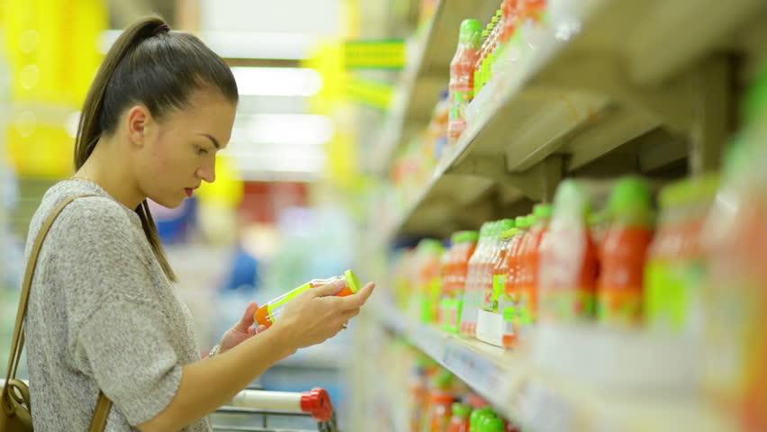 Closeup Portrait of Attractive Young Girl Choosing Juice in the Supermarket Standing Near Shelf. | Shutterstock HD Video #32432980
