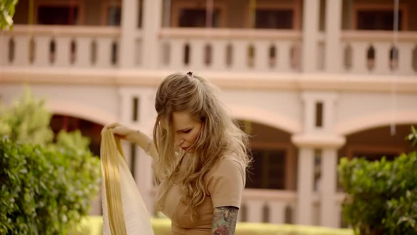 blonde tries on a national silk handkerchief in a hotel in India. tourist pilgrim Krishna