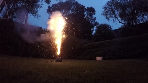 Man launching fireworks explosive pyrotechnic in slow motion in home back yard.  Real people. Copy space